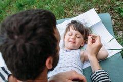 Отец щекоча дочь с травой стоковая фотография rf