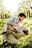 Отец щекочет сына сидя на корточках в траве стоковая фотография rf