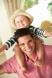 Отец давая езду сынка на плечах внутри помещения Стоковая Фотография RF