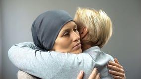Отжатая женщина в головном платке обнимая ее мать, лечение рака, диагноз стоковое фото rf