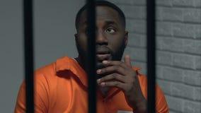 Отжатый Афро-американский пленник в клетке думая о сделанном преступлении, скорбе акции видеоматериалы