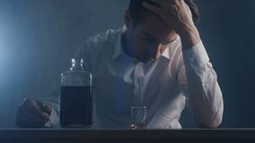 Отжатый бизнесмен льет виски в стопке выпивая самостоятельно в темной комнате Концепция алкоголизма сток-видео