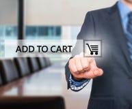 Отжимать бизнесмена добавляет к кнопке тележки на виртуальных экранах Стоковое фото RF