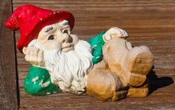 Откалыванный и треснутый но милый декоративный карлик сада при белая борода и красная крышка lounging на деревянной палубе Стоковая Фотография RF