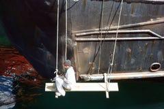 Откалывать ржавчину от грузового корабля на анкере в Бекии Стоковое Изображение
