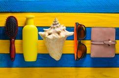 Отклоните аксессуары для релаксации на пляже и красоты на желтом голубом деревянном столе Портмоне, гребень, солнечные очки, рако стоковое фото