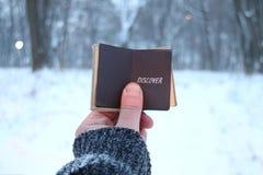 Откройте идею, владения путешественника книга с надписью и снежный парк зимы Запачканные фото для предпосылки стоковое изображение