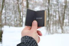 Откройте концепцию Рука держа книгу с надписью На предпосылке леса зимы стоковая фотография
