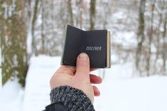 Откройте концепцию Рука держа книгу с текстом На предпосылке леса зимы стоковое фото rf