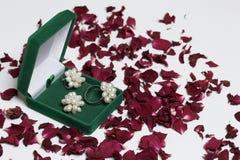 Открытая зеленая коробка бархата для ювелирных изделий В ем лежит комплект: кольцо и серьги с жемчугами На белой предпосылке, пос Стоковое фото RF