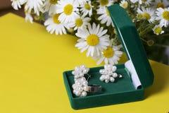Открытая зеленая коробка бархата для ювелирных изделий В ем лежит комплект: кольцо и серьги с жемчугами Рядом с вазой букет chamo Стоковое фото RF