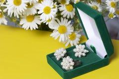 Открытая зеленая коробка бархата для ювелирных изделий В ем лежит комплект: кольцо и серьги с жемчугами Рядом с вазой букет chamo Стоковые Изображения RF