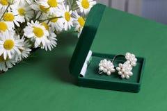 Открытая зеленая коробка бархата для ювелирных изделий В ем лежит комплект: кольцо и серьги с жемчугами Рядом с вазой букет chamo Стоковая Фотография RF