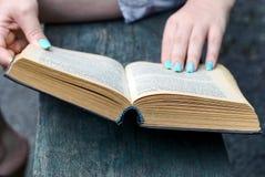 Открытая книга в руках девушки на улице Стоковые Изображения RF
