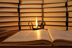 Открытая книга и горящая свеча Освещенная свеча в старом подсвечнике на предпосылке книг стоковые изображения rf