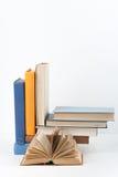 Открытая книга, стог, книги hardback красочные на деревянном столе, белой предпосылке задняя школа к Скопируйте космос для текста Стоковые Фотографии RF