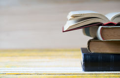 Открытая книга, стог hardback записывает на деревянном столе Стоковое Фото