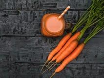 Открытая кружка smoothie моркови и пук морковей на деревенской таблице взгляд сверху Плоское положение Стоковые Изображения