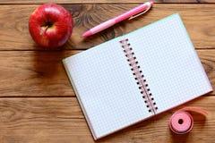 Открытая тетрадь для записи примечаний, ручки, яблока, измеряя ленты в сантиметрах на деревянном столе Разминка и dieting дневник Стоковые Фото