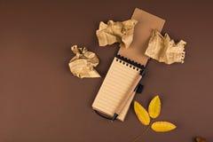 Открытая тетрадь для показателей и скомканных листов на коричневой предпосылке Планирование офиса Открытый космос для текста Атмо стоковые фотографии rf
