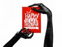 Открытка и счастливая тема хеллоуина: шайка бандитов смерти держа бумажную карточку с словами счастливым хеллоуином на белизне из Стоковые Изображения