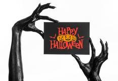Открытка и счастливая тема хеллоуина: шайка бандитов смерти держа бумажную карточку с словами счастливым хеллоуином на белизне из Стоковое Изображение RF