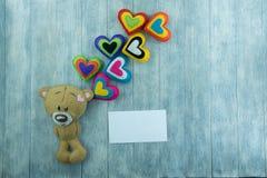Открытка дня валентинок Плюшевый медвежонок и красочные сердца Стоковая Фотография