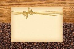 Открытка с золотым смычком на зажаренных в духовке кофейных зернах и деревянное Стоковое Изображение RF