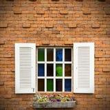 Открытое окно с корзиной цветка на кирпичной стене Стоковая Фотография
