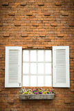 Открытое окно с корзиной цветка на кирпичной стене Стоковые Фотографии RF