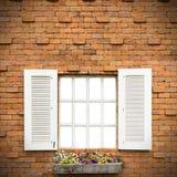 Открытое окно с корзиной цветка на кирпичной стене Стоковые Фото