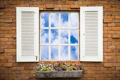 Открытое окно с корзиной цветка на кирпичной стене Стоковые Изображения