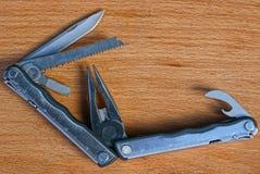 Открытое серое multitool металла лежит на коричневой деревянной доске стоковое фото rf