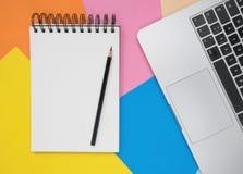 Открытые пустые тетрадь, карандаш и ноутбук на покрашенных бумагах Плоская положенная концепция стола офиса стоковое фото
