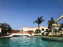 Открытый бассейн с голубыми прозрачными теплыми водой и водными горками на каникулах в тропической теплой экзотической стране, ос стоковая фотография rf