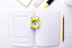 Открытый тетрад-плановик с будильником в центре на белой предпосылке Время сделать дело, космос экземпляра стоковое фото rf