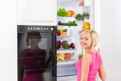 Открыть дверь холодильника женщины Стоковое фото RF