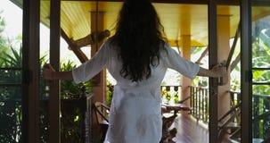 Открыть дверь женщины и идти вне на террасу смотря тропическое вид сзади ландшафта леса назад, привлекательную девушку брюнет видеоматериал