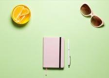 Отклоните плоско таблица места для работы положения женственная с розовым дневником, белой ручкой, Eyeglasses, апельсинами на чаш стоковое фото