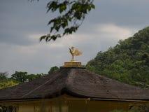 Отливка птицы латунная na górze старого дома стоковая фотография