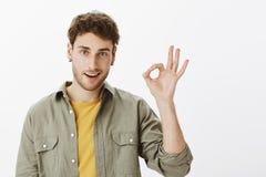 Отлично, одобрите его Портрет красивого и уверенно бородатого парня с вьющиеся волосы, поднимая руку и показывая о'кеы или о'кей стоковая фотография
