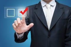 Отметка контрольного списока контрольной пометки касания бизнесмена изолированная на голубой предпосылке Стоковые Фото