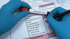 Отметка опухоли, доктор проверяя имена в пробеле лаборатории, показывая пробу крови в трубке видеоматериал