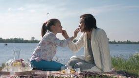 отношение Мат-ребенка, счастливая женщина с одином другого питания дочери во время остатков на пикнике семьи на лужайке видеоматериал