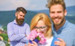 Отношения романс flirt объятий любовников внешние Пары в датировка влюбленности пока жена ревнивого бородатого человека наблюдая  стоковое изображение