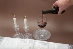 Отображайте вопрос Саббата, дня священного к еврейским людям Вручите лить чашку вина sanctification, и свечи Shabbat освещены Стоковое Изображение RF