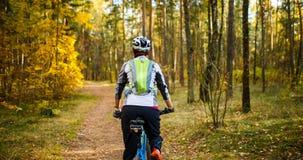 Отображайте от задней части девушки в шлеме на велосипеде Стоковое Изображение