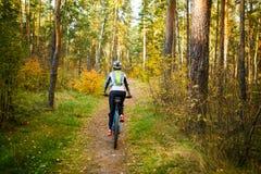 Отображайте от задней части девушки в шлеме на велосипеде Стоковое Фото