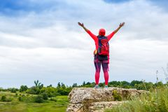 Отображайте от задней части женского туриста при оружия поднятые на холме стоковое изображение rf