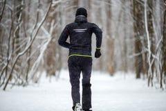 Отображайте от задней части человека в одеждах спорт на беге в зиме стоковое изображение